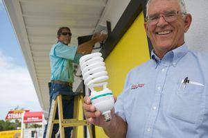 PAUL VIDELA/pvidela@bradenton.com Steve Wilson, right, chief executive officer of Hide-Away Storage, holds a large, 65-watt compact fluorescent bulb, which will soon replace hundreds of 275-watt metal halide bulbs in fixtures throughout Hide-Away's 10 storage facilities. It's one step in an overall energy-savings plan. On the ladder at left is Jimmy Langead, of Goodson Electric of Palmetto, which is helping to rewire the existing light fixtures to accommodate the compact bulbs.